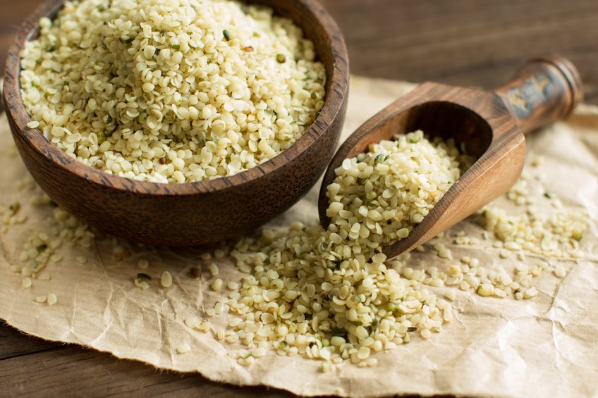 Pile of Uncooked Hemp seeds in a bowl with a spoon