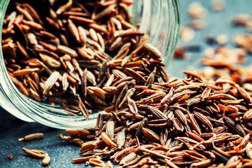 Zira or cumin, oriental spices, grains poured out of a glass jar, black background, macro shot, selective focus