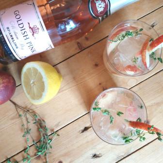 Prosecco cocktail met perzik, tijmsiroop en Goldish Pink